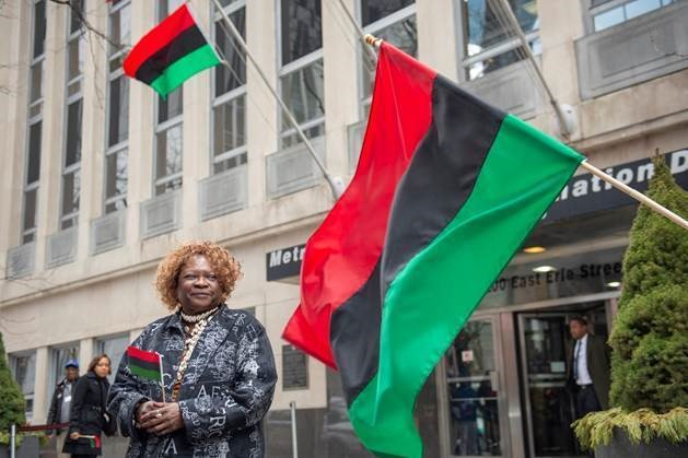Vice President Barbara McGowan stands proudly beneath and next to the African American flag.